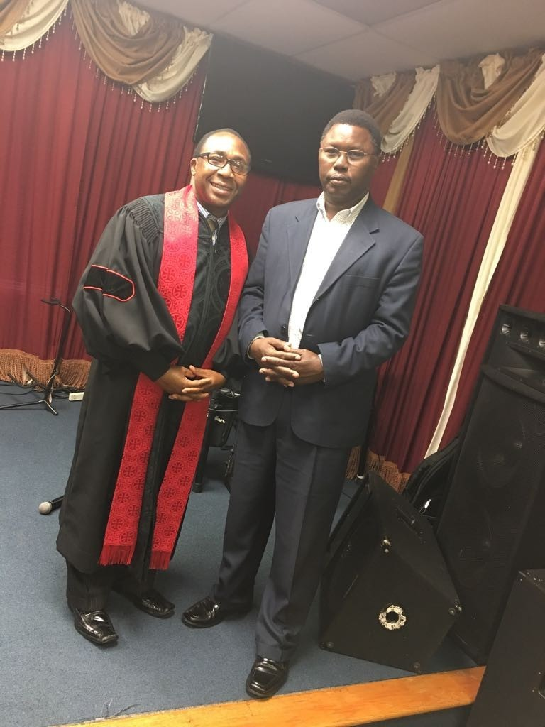 a pastor and a member of the church smiling