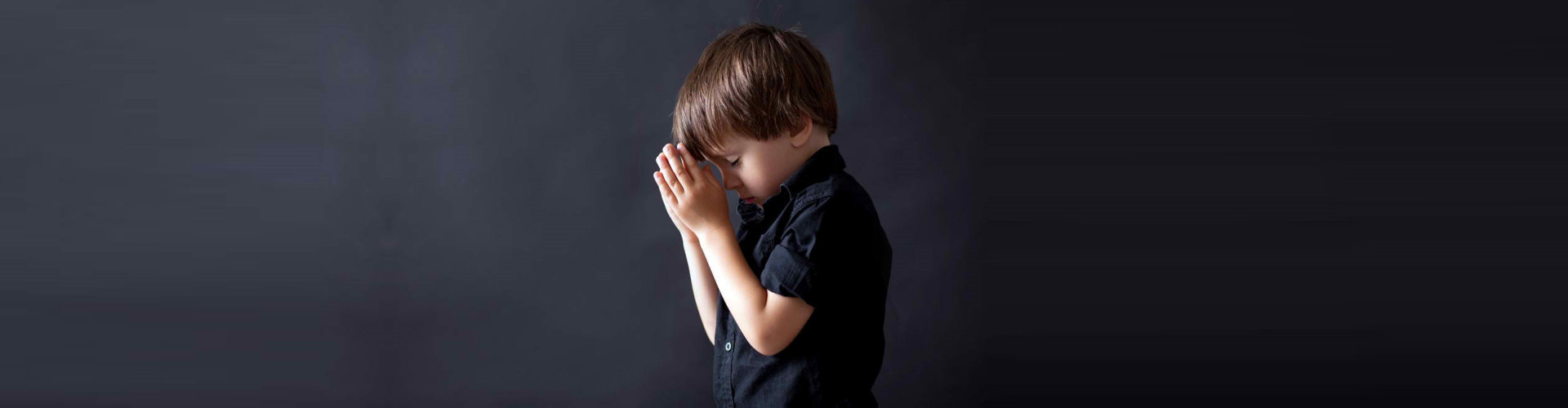 young man praying with clasped hand